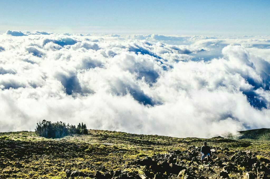 Varied cloud shapes taken right after passing the cloud cover on the way up to Haleakala's summit with man climbing the landscape in the foreground