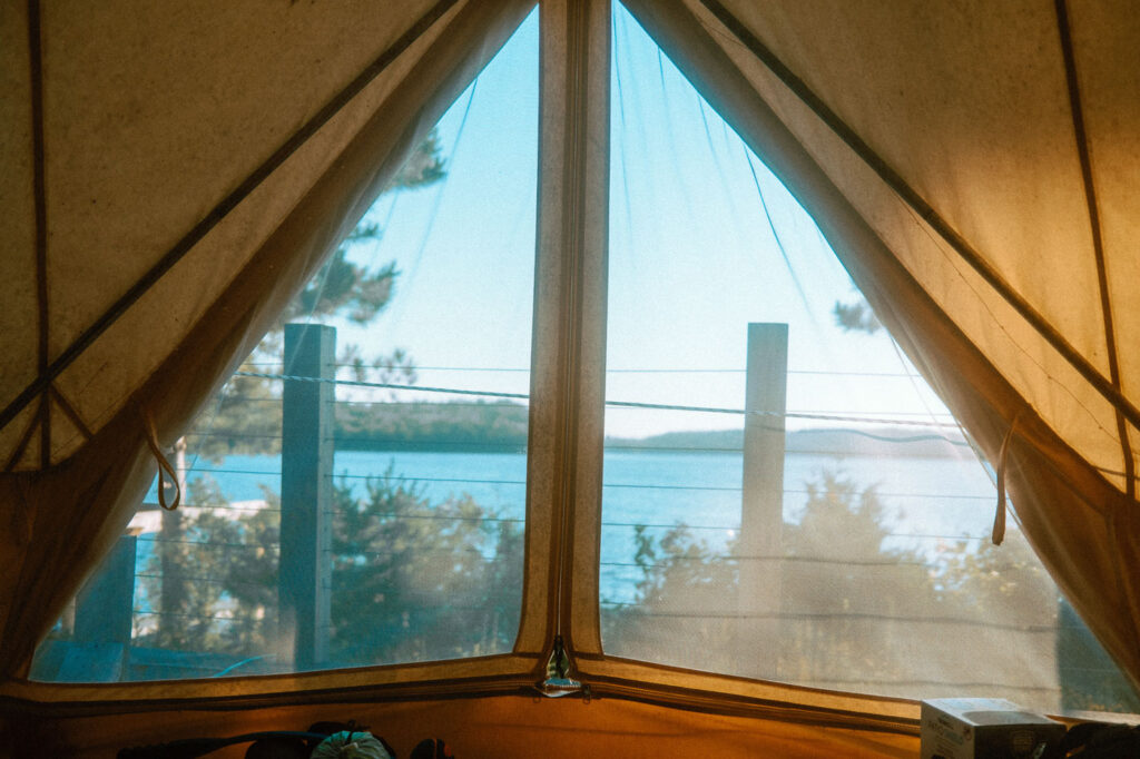 Views of Murray Lake through the vented screen tent doors from inside the glamping tent at Pine Falls Lodge, located in the Greater Sudbury Area (Markstay-Warren)