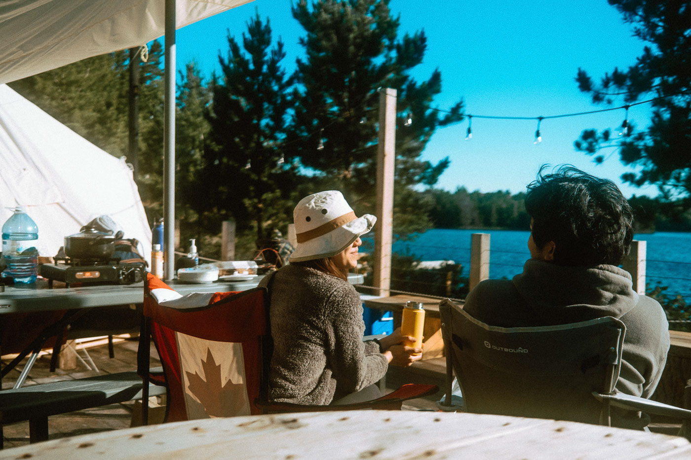 Man and Woman enjoying the glamping tent's private deck at Pine Falls Lodge