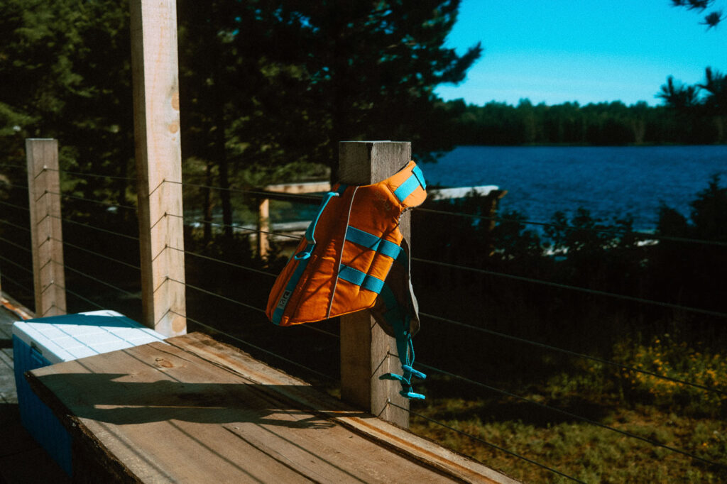 Dog Lifejacket hanging drying on a wooden deck at Pine Falls Lodge