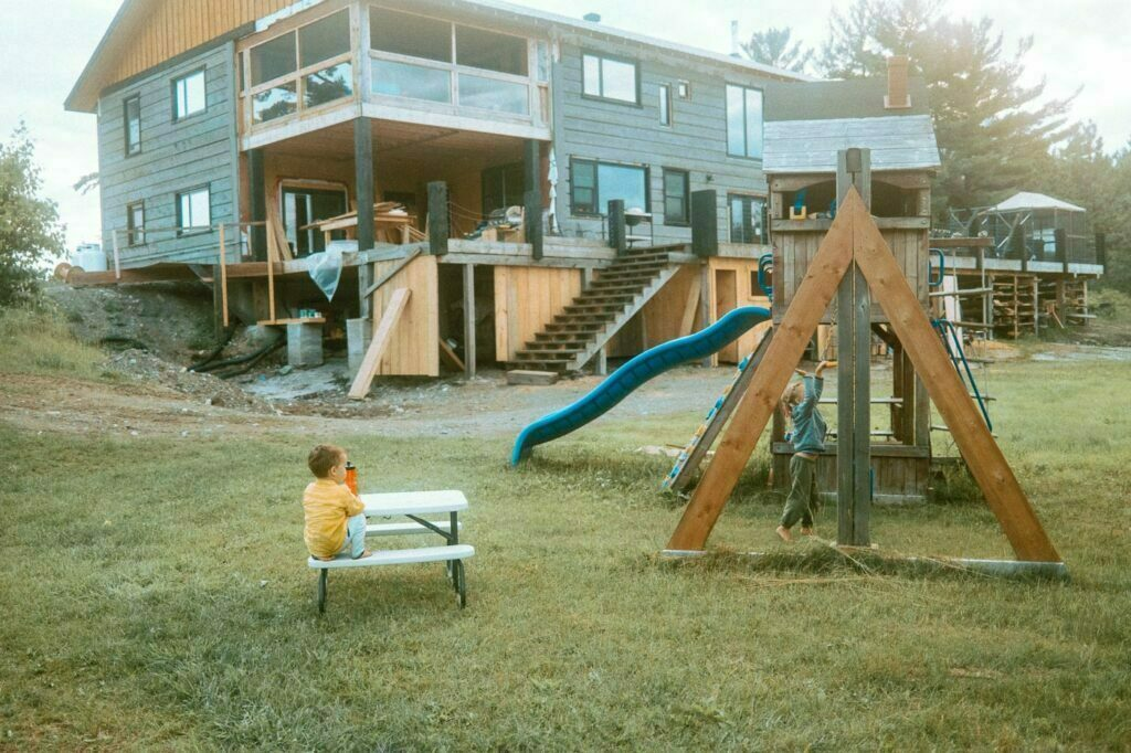 Rear view of the under renovation Pine Falls Lodge with current owner's children playing on the play structure nearby